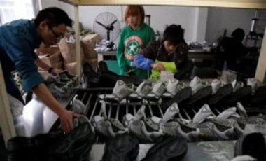 In this photo taken March 18, 2010, Chinese workers assemble sports shoes at a factory in Wenling in south China's Zhejiang province.