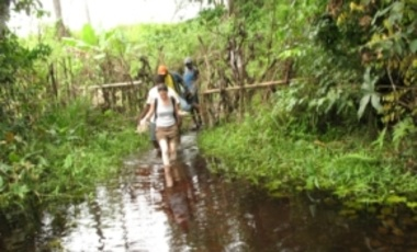 Dara Kay Cohen wades a river to reach her interview location in the Bonthe District in the Southern Province of Sierra Leone.