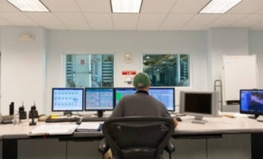 A technician oversees the control center for a public water utility company.