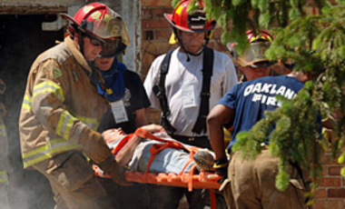 Firefighters remove a victim from a building reduced to rubble at a mock nuclear detonation drill near Butlerville, Ind., May 10, 2007.