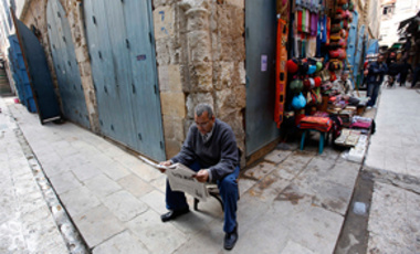 This Thursday Feb. 17, 2011, file photo shows an Egyptian reading a new paper as he sits at an empty street usually busy with tourists in the Khan el-Khalil area of Cairo, Egypt.