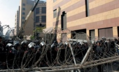 Egyptian riot police stand guard behind barbed wire during clashes near the Egyptian Interior Ministry in Cairo, Feb. 5, 2012, on the fourth day of clashes between security forces and rock-throwing youth after a deadly soccer riot.