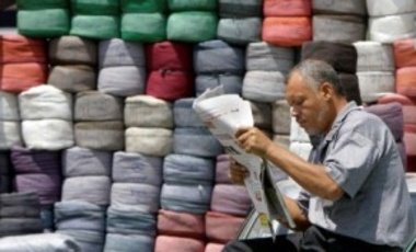 An Egyptian vendor reads a newspaper in front of his stock of colored fabric in Cairo, Egypt, Apr. 23, 2012. Egypt's tourism and investment rates have plummeted and foreign currency reserves have dipped dangerously in the revolution's aftermath.