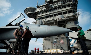 a pilot speaks to a crew member by an F/A-18 fighter jet on the deck of the USS Abraham Lincoln aircraft carrier