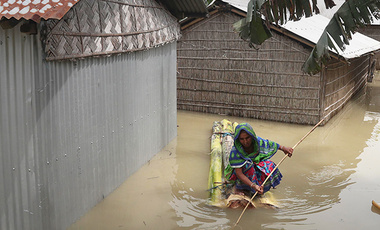 A woman rows a makeshift raft near her partially submerged house in Gagolmari village, Morigaon district, Assam, India, Tuesday, July 14, 2020.