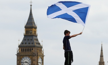 A boy flies a Saltire over the Palace of Westminster