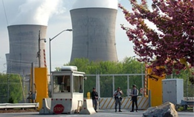 Armed personnel stand in front of the security gate leading to Three Mile Island nuclear power plant in Harrisburg, PA.