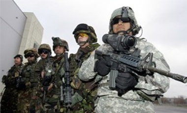 U.S. Army Staff Sergeant Ruben Romero, right, from Fort Benning, Georgia, is joined by soldiers from other NATO countries, as he poses with a new M4 weapon technology making use of a magnifying video camera and thermal imaging.