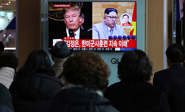 People watch a TV screen showing North Korean leader Kim Jong Un and U.S. President Donald Trump, left, at the Seoul Railway Station in Seoul, South Korea, Friday, March 9, 2018.
