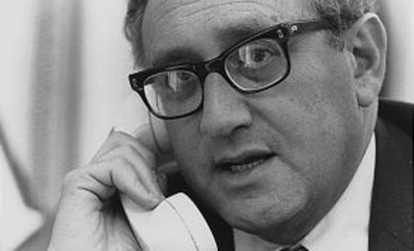 Secretary of State Henry A. Kissinger uses the telephone in Deputy National Security Advisor Brent Scowcroft's office to get the latest information on the situation in South Vietnam, 29 April 1975.