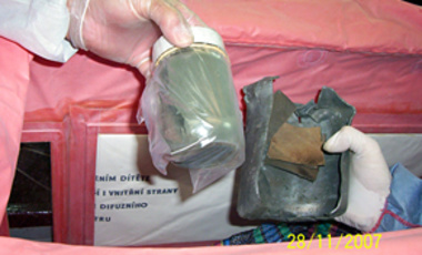 Slovak police experts hold open one of two shells containing 481.4 grams of enriched uranium powder seized in east Slovakia on Wednesday, Nov. 28, 2007.