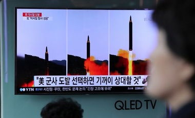 "A woman walks by a TV news program showing images of North Korean missile launch, published in the country's Rodong Sinmun newspaper, at Seoul Railway station in Seoul, South Korea, Monday, May 15, 2017. North Korea said Monday the missile it launched over the weekend was a new type of ""medium long-range"" ballistic rocket that can carry a heavy nuclear warhead."
