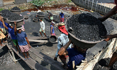 Laborers carry coal to load onto a truck in Gauhati, India, May 29, 2007. Secretary of the Ministry of Environment and Forests Pradipto Ghosh said India will reject proposals to limit GHG emissions because that would hamper its economic growth.