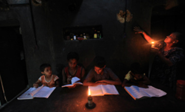 In this May 24, 2011 photograph, Boommi Gowda, extreme right , holds an oil lamp as her children study in their house in Nada, a village near the southwest Indian port of Mangalore, India.