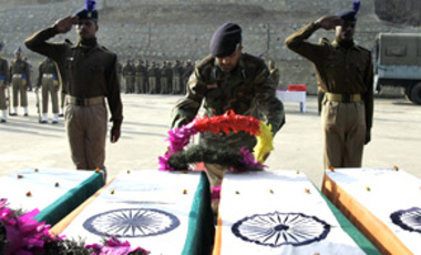 An Indian Paramilitary officer lays a wreath on the coffins of colleagues killed on the outskirts of Srinagar, India, Dec. 31, 2009. Gunmen ambushed and fatally shot 4 Indian paramilitary troops in Kashmir, police said, blaming Muslim militants.