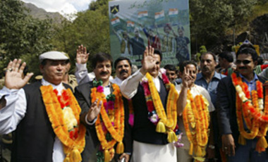 Traders from Pakistani Kashmir wave after crossing onto the Indian side of Kashmir's de facto border, the Line of Control (LoC), Oct. 9, 2008. A delegation of traders from Pakistani Kashmir arrived in Indian Kashmir to hold talks on cross-LoC trade.