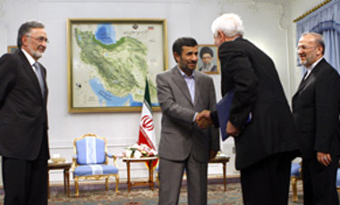 Iranian President Mahmoud Ahmadinejad, center, shakes hands with an unidentified Afghan official during a meeting with Afghan Foreign Minister Zalmai Rasoul, left, as Iranian Foreign Minister Manouchehr Mottaki, looks on, in Tehran, Iran, July 15, 2010.