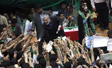 Leading reformist candidate in upcoming Iranian presidential elections, Mir Hossein Mousavi,left, greets his supporters as his wife Zahra Rahnavard, rear right, speaks during a election campaign in Tehran May 31, 2009.