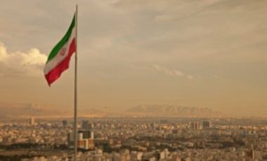 Iranian flag above Tehran's skyline. Iran is a nation-state.
