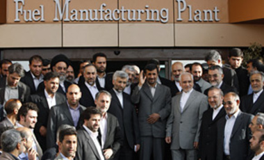 Accompanied by Iranian officials, President Mahmoud Ahmadinejad, waves to the media after inaugurating Iran's Fuel Manufacturing Plant, a new facility producing uranium fuel for a planned heavy-water nuclear reactor, just outside Isfahan, Apr. 9, 2009.