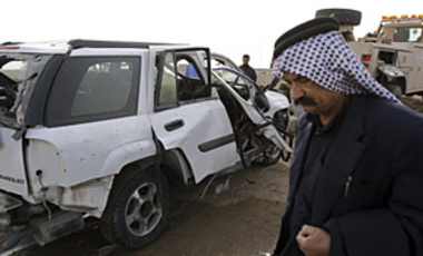 A man stands near a destroyed vehicle after Iraqi border patrol commander Col. Abdul Majeed Mohammed was killed by a bomb placed under his truck near Basra, Iraq, Jan. 20, 2009.