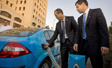 Jerusalem Mayor Nir Barkat, left, and Israeli-U.S. entrepreneur, Shai Agassi, founder a project developing electric cars and a network of charging points, next to an electric car and its charging station in Jerusalem, Oct. 22, 2009.
