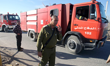 An Israeli officer walks next to Palestinian firefighters, crossing into Israel from the West bank town of Jenin through Al-Jalameh checkpoint, in order to help to extinguish the fire in northern Israel, Dec. 5, 2010.