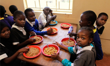 Kenyan school children sit around a table to eat lunch at the Raila Education Center, part of a school feeding program in Kibera, Nairobi. Food prices are rising globally, driven in part by the higher transport costs that accompany rising oil prices.