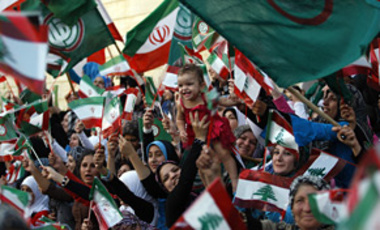 Lebanese Shiite supporters wave Iranian and Lebanese flags at a rally addressed by Iranian President Mahmoud Ahmadinejad in Qana, Lebanon, Oct. 14, 2010. Hezbollah supporters rallied crowds for a visit that took Iran's president near the Israeli border.