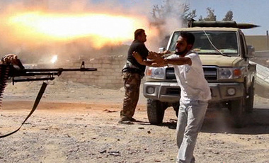 In this video screenshot, fighters from the Islamist Misarata brigade fire towards Tripoli airport in an attempt to wrest control from a powerful rival militia, in Tripoli, Libya, Saturday, July 26, 2014. On Saturday, the U.S. evacuated its diplomats in Tripoli to neighboring Tunisia and shut its embassy.