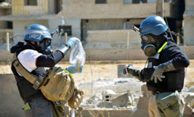 Members of a UN chemical weapons investigation team collect samples after a suspected sarin gas attack in Ain Terma, Syria.