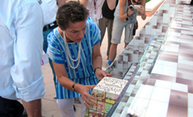 "UN climate chief Christiana Figueres places a building block in a miniature Mayan pyramid at the site of climate negotiations in Cancun, Mexico, Nov. 28, 2010. The ""Pyramid of Hope"" symbolizes the many building blocks needed for a new climate agreement."