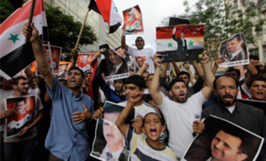 Protesters shout slogans as they carry pictures of President Bashar Assad and national flags, during a demonstration to show their support for the Syrian President, in Beirut, Lebanon, June 11, 2011.