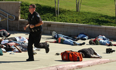 "A police officer runs past ""wounded and dead"" during a mock disaster Oct. 15, 2003, in Bossier City, La. The ""dirty bomb"" scenario involved emergency agencies, the local Office of Homeland Security & Emergency Preparedness, & the U.S. Justice Dept."