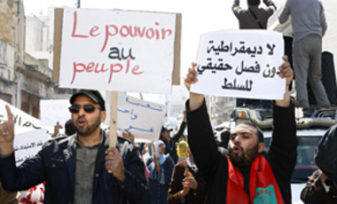 "Thousands of demonstrators with various signs, including at right ""Separation of Powers"" and at left ""Power to People"" during a protest denouncing corruption and demanding better civil rights and a new constitution in Casablanca, Morocco, Mar. 20, 2011,"