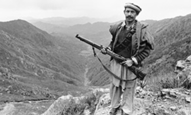 An unidentified Mujahideen rebel stands on guard on high ground over looking the rocky mountainous while on patrol in the area of Kunar Province near the Pakistan border, Feb., 1980, Afghanistan.