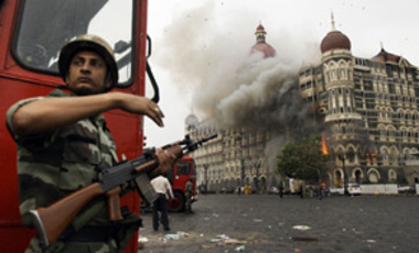 An Indian soldier takes cover as the Taj Mahal hotel burns during gun battle between Indian military and militants inside the hotel in Mumbai, India, Nov. 29, 2008.