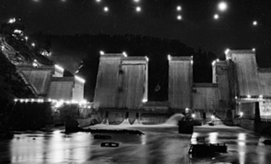 This night view shows the Norris Dam rising from the Clinch River in Norris, Tenn., July 22, 1935. Powerful spotlights placed on and above the dam enable construction work to continue night and day of the Tennessee Valley Authority's project.