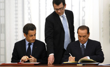 Italian Premier Silvio Berlusconi, right sitting, and French President Nicolas Sarkozy, left sitting, sign a nuclear cooperation agreement at a ceremony in Rome's Villa Madama residence, Feb. 24, 2009.
