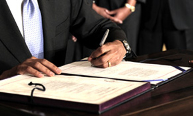 President Barack Obama signs the Iran Sanctions Bill imposing tough new sanctions against Iran as further punishment for the country's continuing nuclear program, July 1, 2010, in the East Room of the White House.