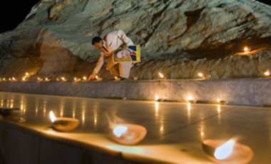 A supporter of Pakistan Muslim League-N party arranges an oil lamp at the model of Chaghi Mountain, the site of Pakistan's nuclear test, in connection with the celebrations of its 10th anniversary, May 27, 2008 in Islamabad, Pakistan.