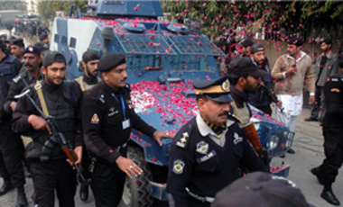 Pakistani police officers escort an armored car carrying Mumtaz Qadri, the alleged killer of Punjab governor Salman Taseer, to an Anti-Terrorist Court in Rawalpindi, Pakistan, Jan. 6, 2011.