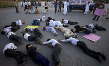Shia youths from the Pakistani Kurram tribal area stage a mock scene during a rally demanding peace in their region, near the Presidential House, in Islamabad, Pakistan, Apr. 25, 2011.