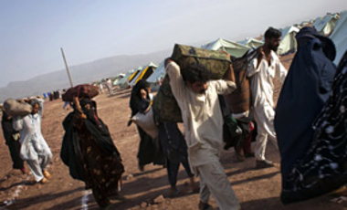 A displaced Pakistani family carry their belongings as they arrive in Jalozai refugee camp after fleeing fighting in the Swat valley, June 7, 2009.
