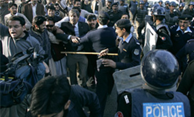 Pakistani police officers block journalists from marching during a rally against the country's military ruler President Gen. Pervez Musharraf