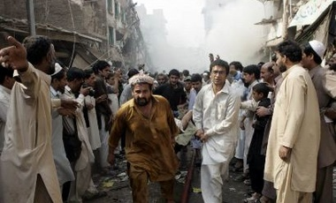 Rescue workers rush an injured person to a hospital in Peshawar, Pakistan on Wednesday Oct. 28, 2009. A car bomb has torn through a market popular with women in northwestern Pakistan.