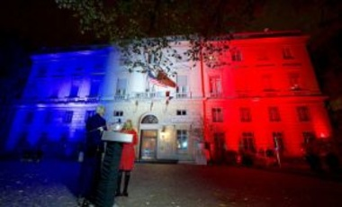 U.S. Secretary of State John Kerry, joined by U.S. Ambassador to France Jane Hartley, looks at the U.S. Embassy in Paris in the French tricolor after he lit it on November 16, 2015, in a sign of solidarity following the November 13 terrorist attack.