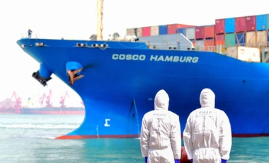 Workers in protective suits stand by a container ship in Qingdao, China, March 31.
