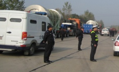 Armed guards and police protecting a spent fuel convoy while at a stopping point.