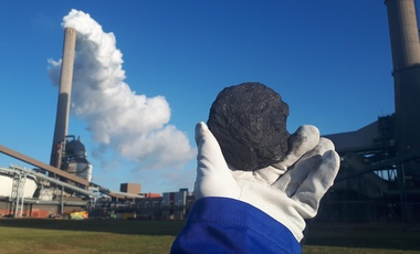 Worker holding up a piece of coal in front of a coal-fired power plant in the Netherlands